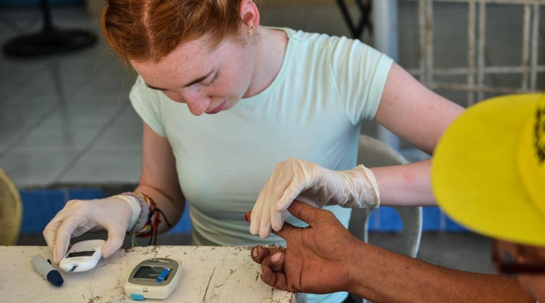 A female Projects Abroad intern during an outreach is taking blood sugar levels of various patients whilst on her medical internship in the Phillippines.